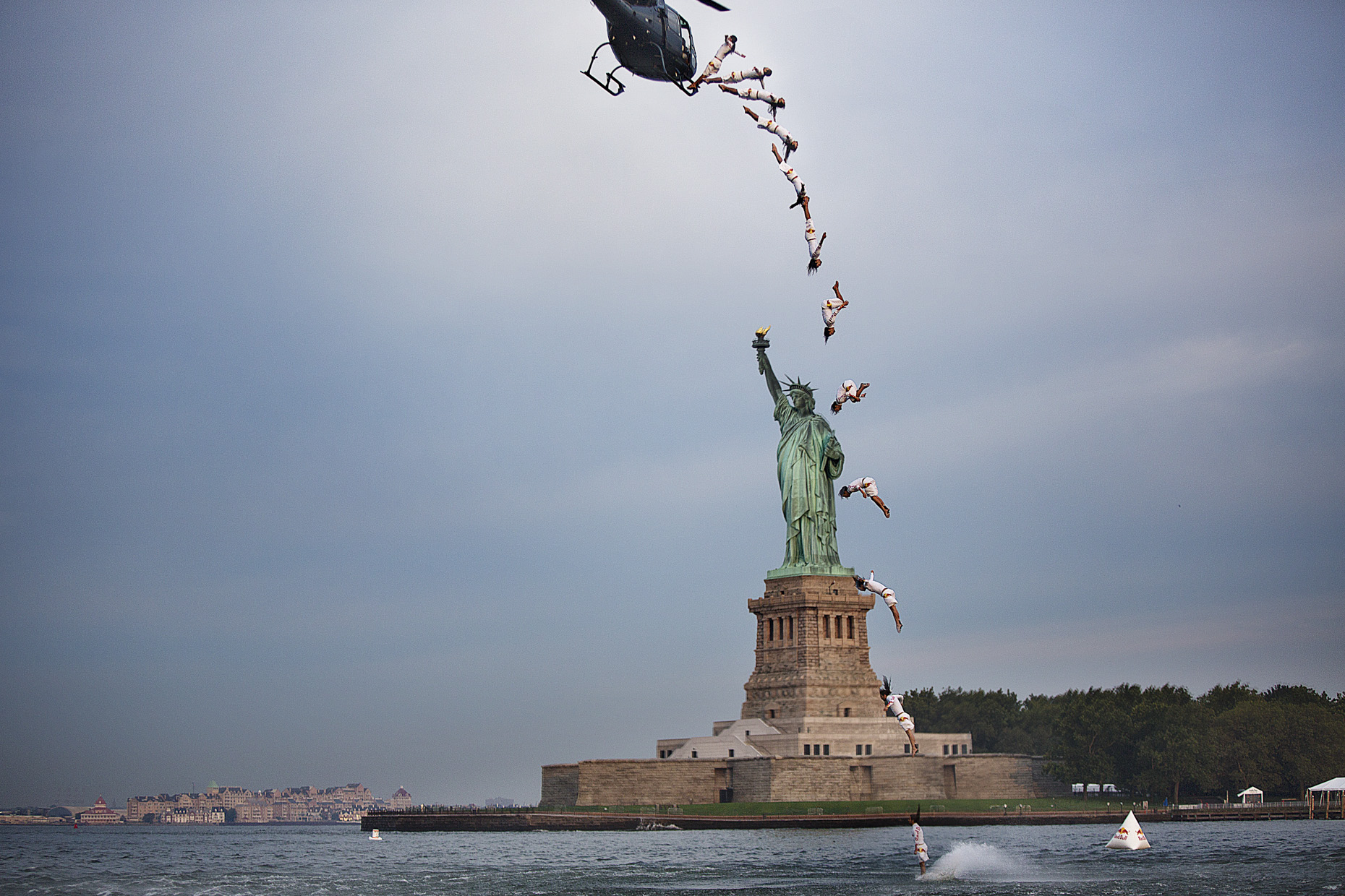 Orlando Duque cliff dives in front of the statue of Liberty in NYC for Red Bull by Boston based commercial sports photographer Brian Nevins