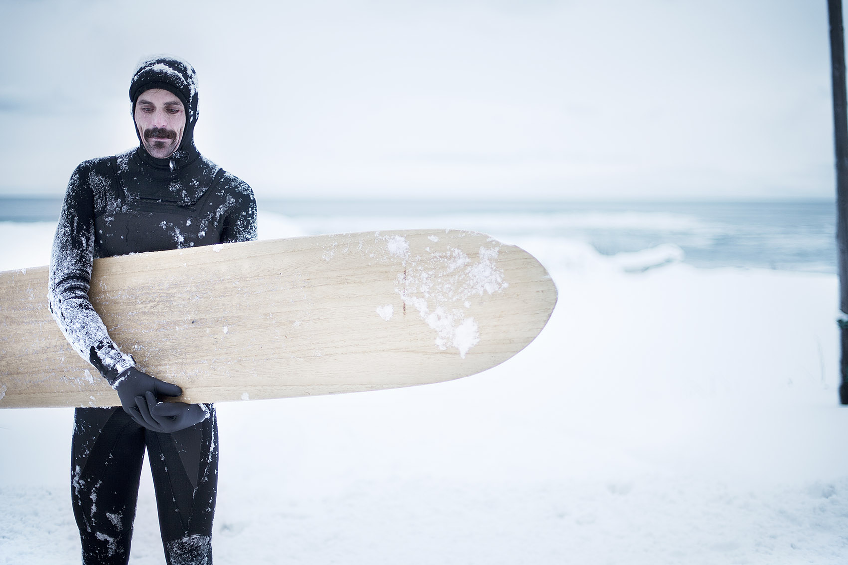 Dan Malloy holds his Alia board in Hokkaido, Japan during a snowstorm by Boston based commercial lifestyle photographer Brian Nevins