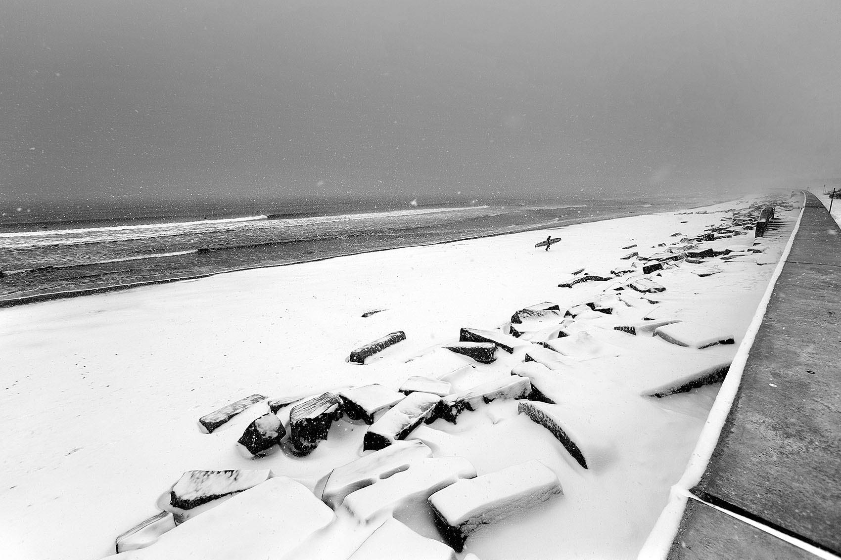 Surfer in the snow at the wall in Hampton, New Hampshire by Boston based commercial lifestyle photographer Brian Nevins